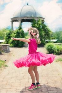 little girl twirling, dancing, outdoors